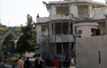 People stand around a bombed-out building