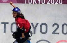 """Sakura Yosozumi is shown wearing a red shirt and purple helmet while skateboarding down a wall with """"Tokyo 2020"""" painted on it."""
