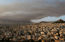 A view of Athens from above showning the city and in the distance large dark smoke clouds filling the sky.