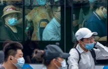 Several people are shown through the window's of a crowded bus with many wearing blue medical masks.