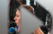 Belarusian Olympic sprinter Krystsina Tsimanouskaya is shown through a frosted glass window speaking into microphones.