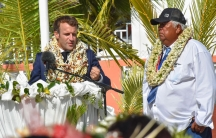 France's President Emmanuel Macron wears a flowers leis and seashell necklaces gestures as he speaks up on his arrival as the mayor Manihi John Drollet stands next to him at the Manihi Atoll, 312 miles northeast of Tahiti, French Polynesia.