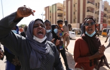 Two women are shown at the head of a group of protesters, one with her hand rised in the air.