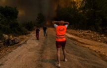 A man is shown with his back to the camera and facing a large wildfire with two other people running away from the fire.