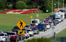 A line of vehicles wait to cross the Canadian border in view of a Canadian flag made of flowers