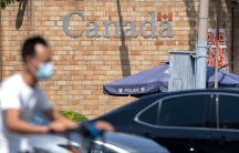 A man is shown riding a scooter in blurred focus while wearing a facemask with the brick facade of the Canadian embassy building in the distance.