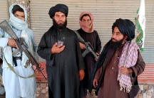 Four men are shown wearing traditional Afghani robes with two men holding large weapons.