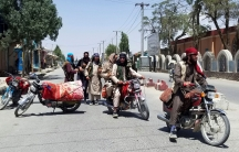 Several Taliban fighters are shown standing in a street or sitting on blanket-covered motorcycles.