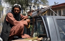 A Taliban fighter sits on the back of a vehicle with a machine gun in front of the main gate leading to the Afghan presidential palace