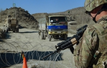 A USsoldier with Apache Company of Task Force 3-66 Armor, out of Grafenwoehr, Germany, stands guard at a police checkpoint at Gulruddin pass in Sar Hawza district of Paktika province, south of Kabul, Afghanistan, Dec. 1, 2011.