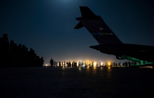 A line of people are shown in the distance in low light with the tail of a large aircraft as the sun sets.