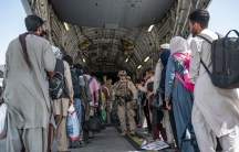 In this Aug. 21, 2021, image provided by the U.S. Air Force, US Airmen and U.S. Marines guide evacuees aboard a US Air Force C-17 Globemaster III in support of the Afghanistan evacuation at Hamid Karzai International Airport in Kabul, Afghanistan.