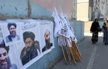 Afghan women walk by posters of Taliban leaders and flags in Kabul, Afghanistan, Wednesday, Aug. 25. 2021.
