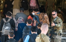 US Air Force airmen guide evacuees aboard a US Air Force C-17 Globemaster III at Hamid Karzai International Airport in Kabul, Afghanistan