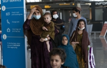 Families evacuated from Kabul, Afghanistan, walk through the terminal before boarding a bus after they arrived at Washington Dulles International Airport, in Chantilly, Virginia, Aug. 27, 2021.