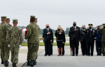 A group of military personel are shown carrying a flag-drapped coffin and walking toward US President Joe Biden and other cabinet officials.