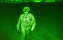 A US military officer is shown wearing full combat gear under the green light of a night goggle lens.