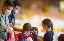 Two men are shown wearing medical face masks and handing out drink boxes and snacks to two young Afghan refugees.