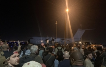 Crowd at night gathered around a Luftwaffe transport plane