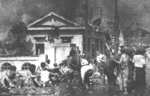 A crowd of survivors are shown standing and sitting on a bridge with several damaged buildings in the distance.