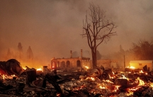 Buildings burn as the Dixie Fire tears through the Greenville community of Plumas County, Calif., on Wednesday, Aug. 4, 2021.