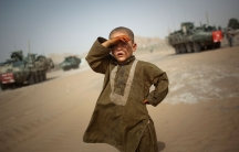 A young boy is shown with his right hand up to his face shielding the sun with armored military vehicles shown in the distance.