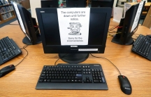 In this Aug. 22, 2019, file photo, signs on a bank of computers tell visitors that the machines are not working at the public library in Wilmer, Texas.