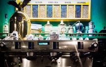 An espresso machine with coffee beans from around the world featured in the background.