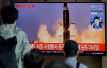 Three people are shown from behind looking at a television that has a large missile with smoke and fire from its launch.