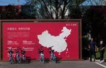 People walk by a map showing Evergrande development projects in China at an Evergrande new housing development in Beijing, Wednesday, Sept. 22, 2021.