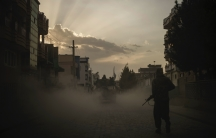 A Taliban fighter walks on the side of a road as a Humvee carrying other fighters drives by in Kabul, Afghanistan, Sept. 21, 2021.
