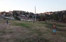 Teenage boys fly kites in an open field in Rio de Janeiro, Brazil.