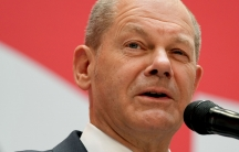 Olaf Scholz is shown in a close-up photoographer standing behind a microphone.