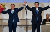 Fumio Kishida, right, is shown with his arms raised celebrating with Yoshihide Suga who is standing next to him.