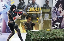 A child plays with a toy gun during a promotion for online games in Beijing onAug. 29, 2020. China is banning children from playing online games for more than three hours a week, the harshest restriction so far on the game industry as Chinese regulators