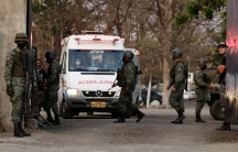 A white ambulance is shown from the front with several people wearing military fatigues and carrying weapons standing nearby.