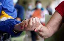 Residents Ken Fishman, 81, left, and Esther Wallach, 82, right, hold hands as they wait in line for the Pfizer-BioNTech COVID-19 vaccine at the The Palace assisted living facility in Coral Gables, Florida