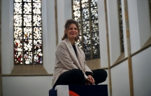 Kunsthalle Osnabrück co-director Anna Jehle sits near colorful stained-glass windows inside a church.