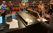 Group of people stand around a pianist in an auditorium