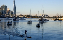 A man is shown on his stand up paddle board with several boats docked in the distance along with Sydney's skyline.