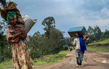 A women is shown in the nearground carrying large sacks over her back and walking with a man in the distance carrying a large blue crate.
