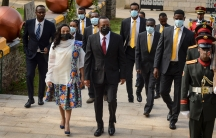Ethiopia's Prime Minister Abiy Ahmed is shown wearing a suit a face mask while walking next to First Lady Zinash Tayachew who is wearing a white and flower print dress.