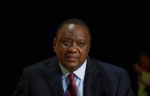 Kenya's President Uhuru Kenyatta is shown sitting and listening while wearing a dark suit and red tie.