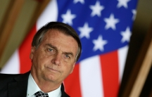 Brazil's President Jair Bolsonaro stands in front of a US flag during a news conference at Itamaraty Palace in Brasilia, Brazil, Tuesday, Oct. 20, 2020.