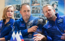 A woman and two men are sitting next to each other wearing blue Russian cosmonaut uniforms with the middle person holding a microphone.