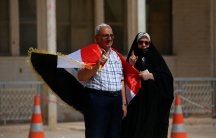 A man and his wife show their ink-marked fingers after casting their votes inside a polling station in the country's parliamentary elections in Najaf, Iraq