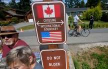 A family visits across the U.S.-Canada border at the Peace Arch Historical State Park as a cyclist rides past on the Canadian side, in Blaine, Wash.