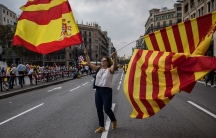 """A woman waves flags of Catalonia and Spain as people celebrate a holiday known as """"Dia de la Hispanidad"""" or Spain's National Day in Barcelona, Spain, Thursday, Oct. 12, 2017."""