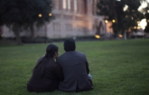 A man and a women sit on the grass together at twilight