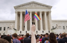 Arm holds up an American flag and a pride flag outside the US Supreme Court